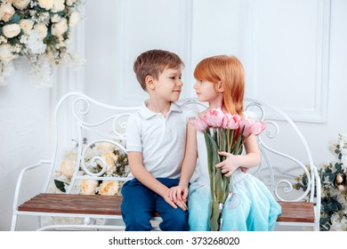 Funny kids, happy little boy giving a cute girl bouquet of yellow spring flowers. Series in studio. Valentines Day, Mother's Day, 8 March, the birthday, the International Women's Day