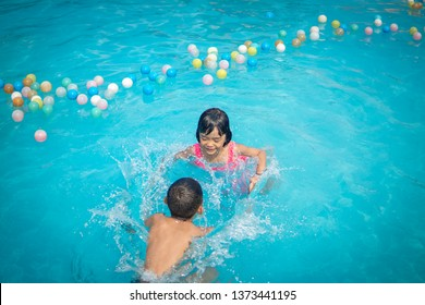 Funny kids summer concept, kid swimming and playing in swimming pool on summer holidays time