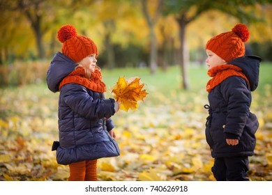 Funny kids twins in red hat in autumn park