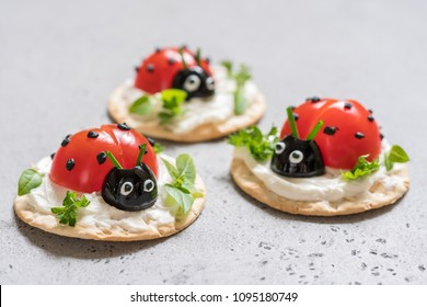 Funny Ladybird Snack Appetizer with Tomato on Crackers