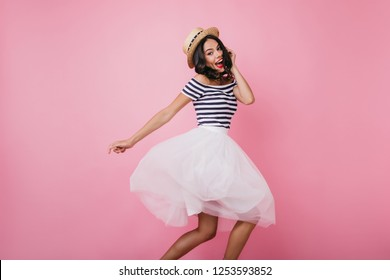 Funny latin woman in straw hat expressing happiness and dancing. Emotional female model in white skirt posing on pastel background.