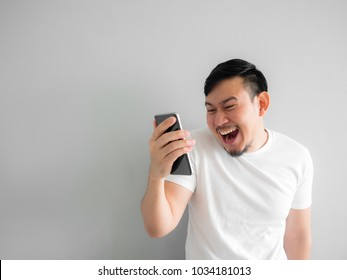Funny laugh face of Asian man watching funny video clip share in social in the smartphone.
