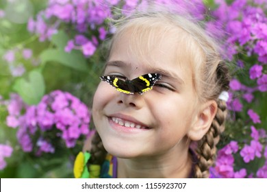 Funny laughing 5-6 years old girl with a butterfly on her nose, happy summertime and childhood, outdoor