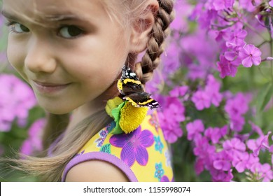 Funny laughing 5-6 years old girl with a butterfly on her nose, happy summertime and childhood, outdoor, focus on batterfly