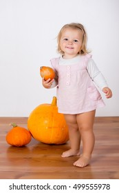 Funny laughing baby girl playing with a huge pumpkin