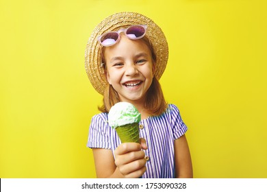 Funny laughing caucasian child girl with ice cream, close-up shot on yellow isolated background.