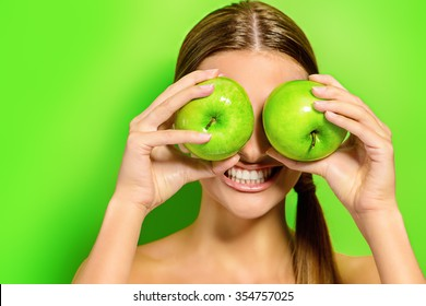 Funny laughing woman holding two gren apples before her eyes. Green background. Healthy eating concept. Diet.