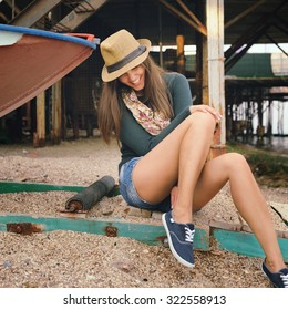 Funny laughing young woman with long legs looking on her gumshoes under the old pier, autumn outdoor.