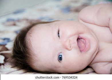 Funny laughting infant portrait lying on bed, happy smiling baby winking