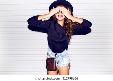 Funny lifestyle portrait of crazy girl closed her eyes,emotional and happy mood,chic clothes and summer hat outdoors.Soft warm vintage color tone.Stylish sweater and hat.smiling laughing,autumn colors
