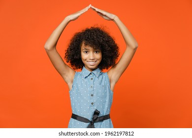 Funny little african american kid girl 12-13 years old in denim dress hold hands above head like roof of house isolated on orange background children studio portrait. Childhood lifestyle concept