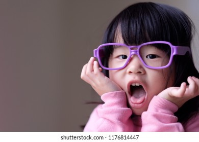 Funny little asian child with a pair of big purple glasses