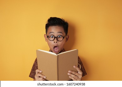 Funny little Asian student boy shocked with tongue sticking out when reading a book, secret book, educational concept