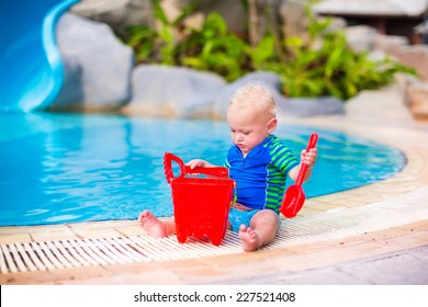Funny little baby boy in sun protection shirt and swimming diaper playing with a red toy bucket at a pool in a tropical resort
