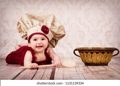 Funny little baby chief  crawling on the floor, smiling and holding wooden spoon