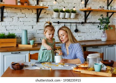 Funny little baby helper playing with dough on his hands learning to knead helps adult mom in the kitchen, happy cute baby daughter and parent mom have fun cooking cookies.