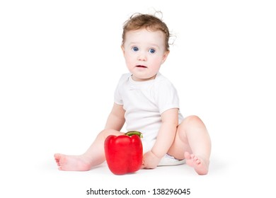 Funny little baby playing with a red paprika