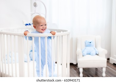 Funny little baby standing in round modern bed with mobile in white nursery with window. Infant boy in blue pajamas with teddy bear toy. Nursery interior for young child. Kids sleep wear and bedding