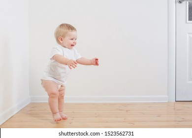 funny little  baby takes first steps on wooden floor
