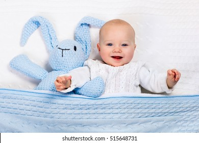 Funny little baby wearing a warm knitted jacket playing with toy bunny relaxing on white cable knit blanket in sunny nursery. Kids winter clothing and bedding. Hand made toys and textile for children.