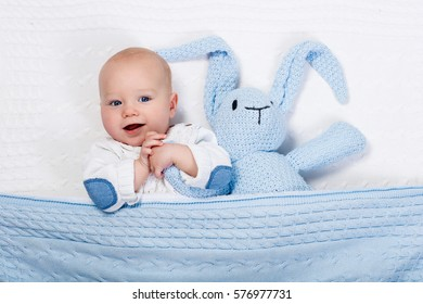 Funny little baby wearing a warm knitted jacket playing with toy bunny relaxing on white cable knit blanket in sunny nursery. Kids winter clothing and bedding. Hand made toys and textile for children