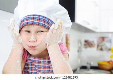 Funny little baker grimaces in the kitchen