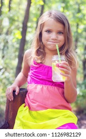 Funny little blond girl making funny faces while drinking lemonade