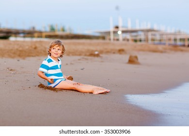 Funny little blond kid boy having fun with building sand castle on the beach of ocean or sea by sunset. Happy child spending active vacations.