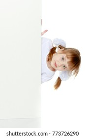 Funny little blonde girl with pigtails and white bows on her head in a white T-shirt and shorts.She hid behind the white banner ad and peeks out because of him.