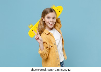 Funny little blonde kid girl 12-13 years old in casual yellow jacket posing isolated on blue background studio. Childhood lifestyle concept. Mock up copy space. Hold skateboard, showing victory sign