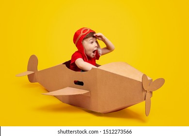 Funny little boy in aviator hat keeping hat near forehead and looking away with amazed face expression while piloting cardboard plane against yellow background