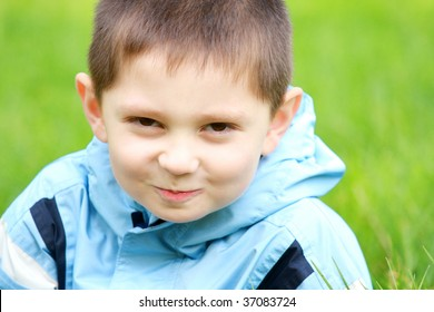 Funny little boy in blue jacket outdoor closeup portrait