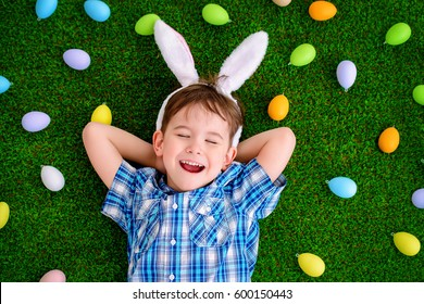 Funny little boy with bunny ears lying on a grass among colorful Easter eggs. Easter holiday.