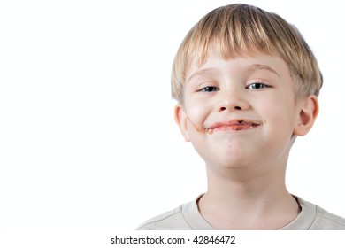 funny little boy with chocolate on the face  isolated on white