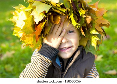 Funny little boy covered his eyes with his hand