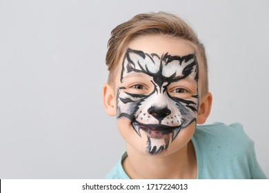 Funny little boy with face painting on light background