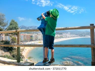 Funny little boy looking in telescope at Lloret beach. Lloret de Mar. Catalonia, Costa Brava, Spain, Europe