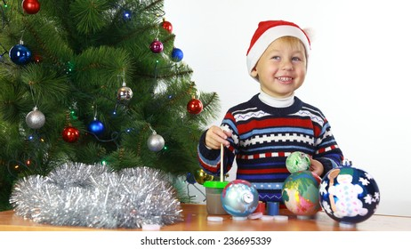 Funny little boy painted with Christmas balls