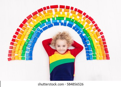 2d72df84ffd9 Funny little boy playing with colorful rainbow plastic blocks. Kids play