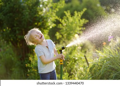 Funny little boy playing with garden hose in sunny backyard. Preschooler child having fun with spray of water. Summer outdoors activity for kids.