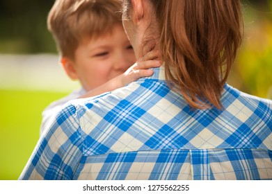 A funny little boy plays with his mom and says something to her while walking in a sunny city park. Child care oncept
