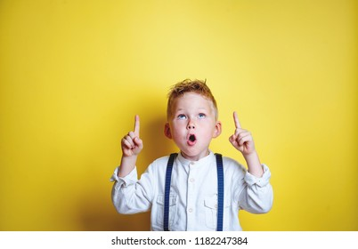 Funny little boy pointing up on yellow background. Portrait of stylish little child with finger pointed up. Success, bright idea, creative ideas and innovation technology concept.