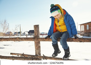 funny little boy sitting on a fence. child on a walk in the winter.