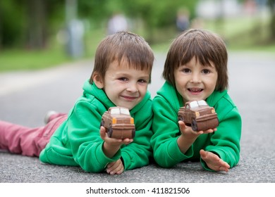 Funny little boys playing with car of chocolate, outdoor, having fun