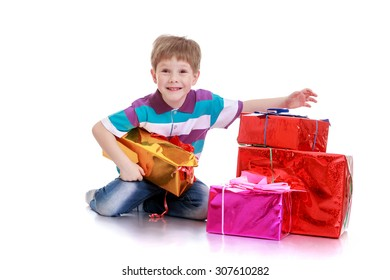 Funny little brown-eyed boy sitting on the floor. Next to the boy lay the box with gifts-Isolated on white background