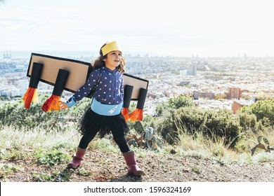 funny little child girl flying disguised as a superhero with homemade costume and cardboard plane wings in front of a cityscape, imagination and girl power concept