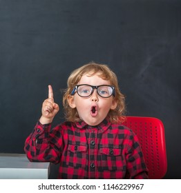 Funny little child in glasses pointing up. Kid with blackboard on background. Pupil from primary school. first day of fall. Education, Success, bright idea, creative idea.