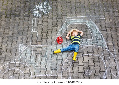 Funny little child having fun with tractor picture drawing with chalk.