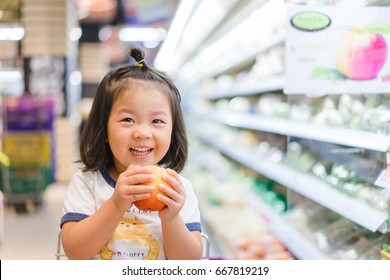 Funny little child smile and holding apple.Asian kid Shopping in supermarket.Little asian toddler girl sitting in the trolley during family shopping in hypermarket.