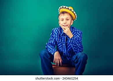Funny little child traveler wearing sombrero sitting on suitcase. Travel and vacation concept.